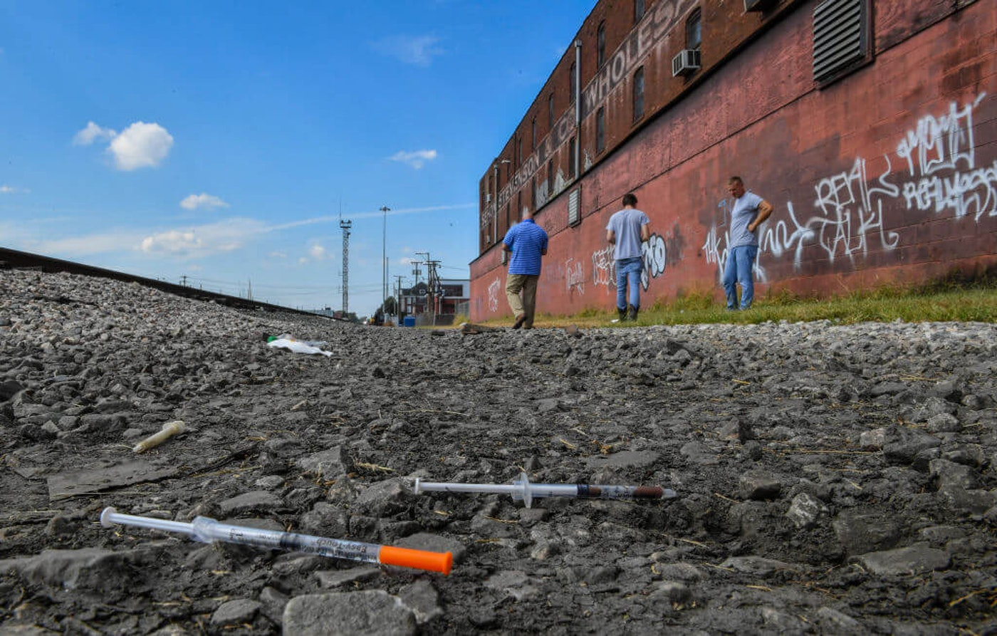 Two partially used syringes and needles are seen as Rocky Meadows, left, former addict and founder of Lifehouse treatment and recovery center, walks with two former addicts along rail tracks where addicts use drugs on October 2, 2019 in Huntington, WV. (Photo by Ricky Carioti/The Washington Post via Getty Images)