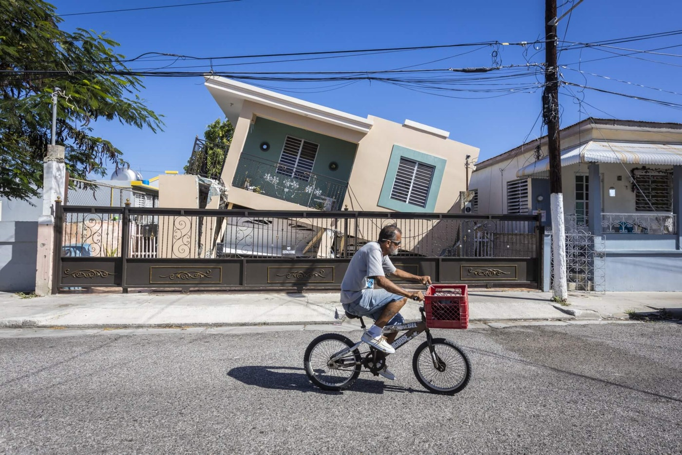 A man rides his bike in front of a collapse house after 6.4-magnitude earthquake hit Guanica, Puerto Rico on January 11, 2020.
