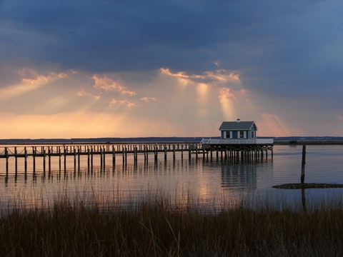 Pier with small house on the water at sunset