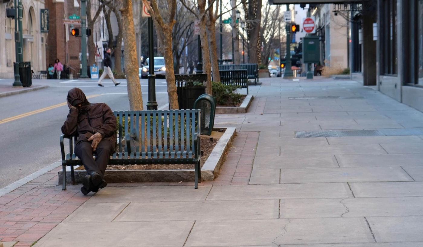 Rough looking man sitting on bench, bundled up, sleeping.
