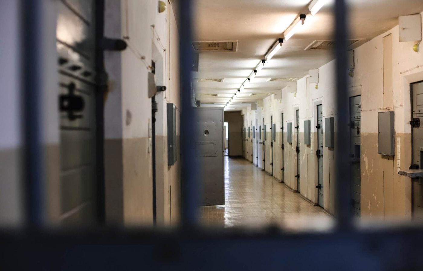 Empty jail cellblock hallway with an open door
