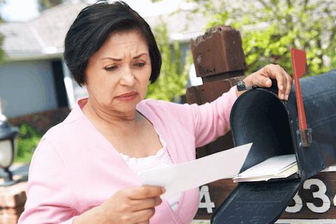 Photo of a worried senior hispanic Virginia women checking her mail in the mailbox.