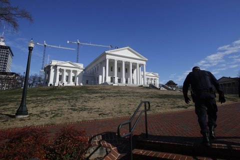 A police officer walks up to the Virginia State Capitol in Richmond, Va. Due to concerns over coronavirus, the Capitol will close to visitors and staff until the end of March 2020. (AP Photo/Steve Helber, File)