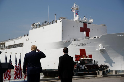 President Donald Trump salutes as the U.S. Navy hospital ship USNS Comfort pulls away from the pier at Naval Station Norfolk in Norfolk, Va., Saturday, March 28, 2020. The ship is departing for New York to assist hospitals responding to the coronavirus outbreak. Defense Secretary Mark Esper is at right. (AP Photo/Patrick Semansky)