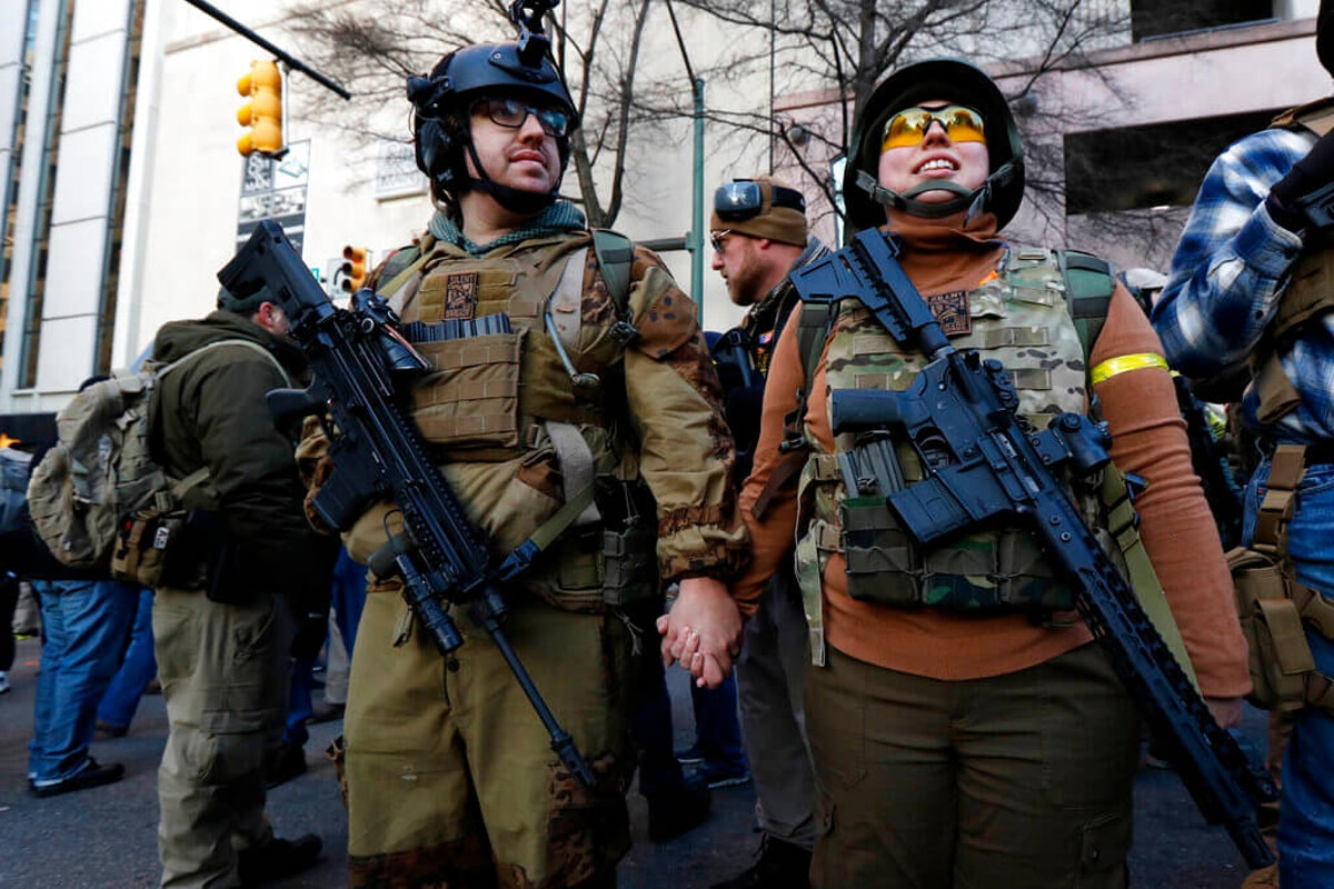 In this Jan. 20 photo, demonstrators stand outside a security zone before a pro-gun rally in Richmond, Va. Gov. (AP Photo/Julio Cortez, File)