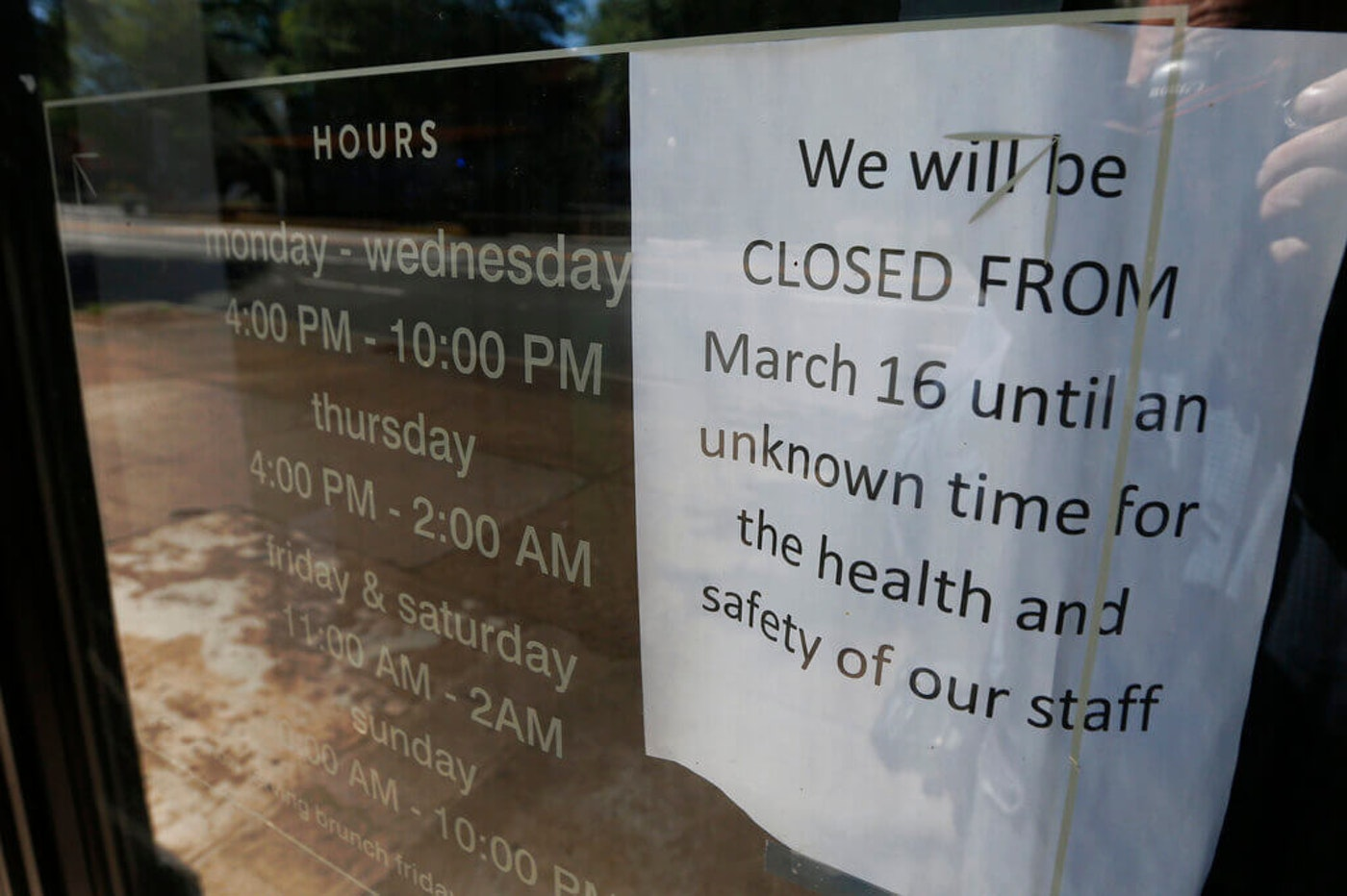 A sign is posted on the front door of the closed Tarrant's Café restaurant in Richmond, Va. More than two months after the coronavirus pandemic started forcing Virginia businesses to slash their workforces, the state's unemployment system still can't keep up with the unprecedented deluge of calls and emails from laid-off workers who need help. (AP Photo/Steve Helber, File)