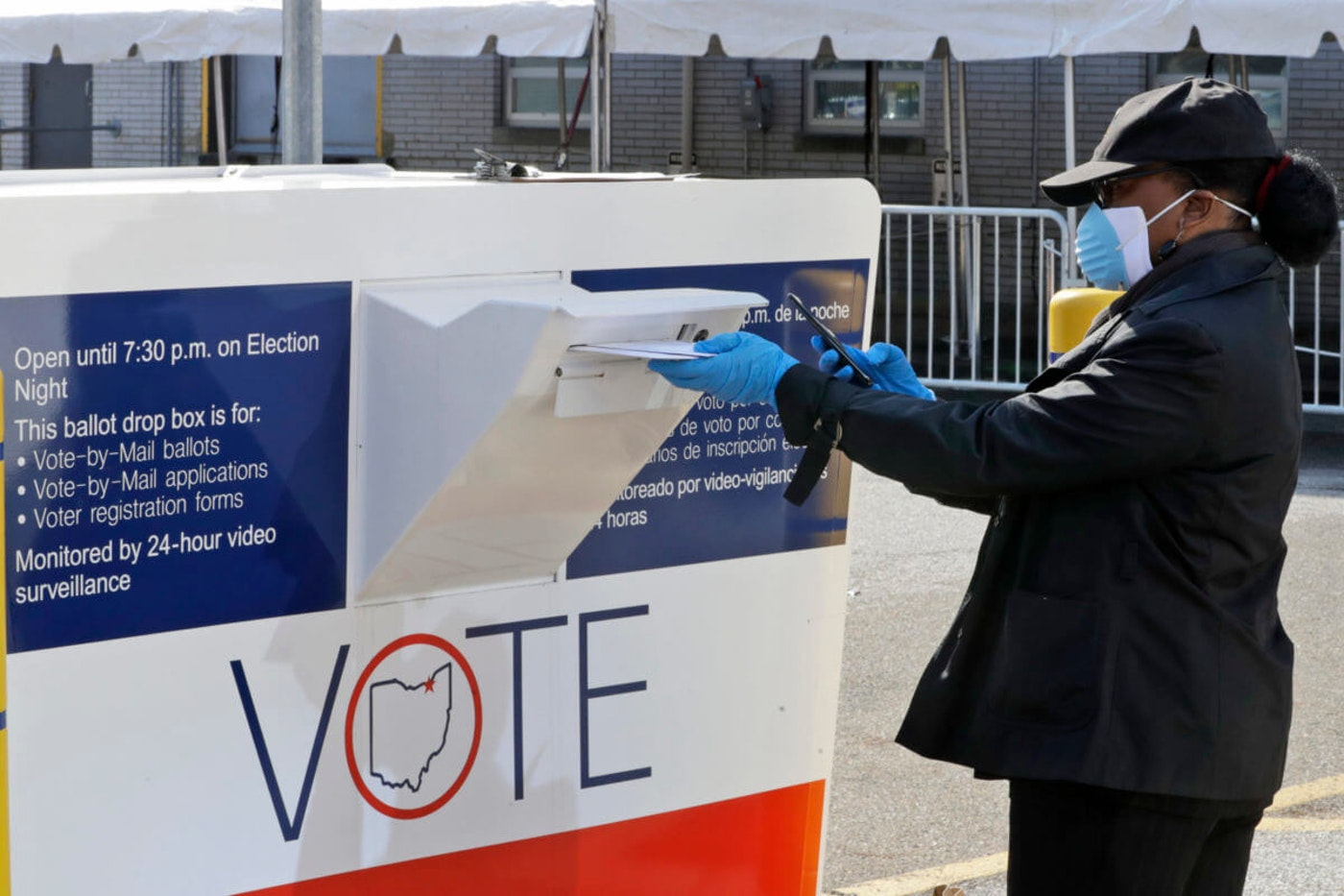 Marcia McCoy drops her ballot into a box outside the Cuyahoga County Board of Elections. (AP Photo/Tony Dejak)