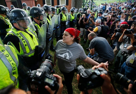 A protester confronts riot gear-clad police on the campus of the University of Virginia during a rally to mark the anniversary of the Unite the Right rally in Charlottesville, Va., Saturday, Aug. 11, 2018. (AP Photo/Steve Helber)