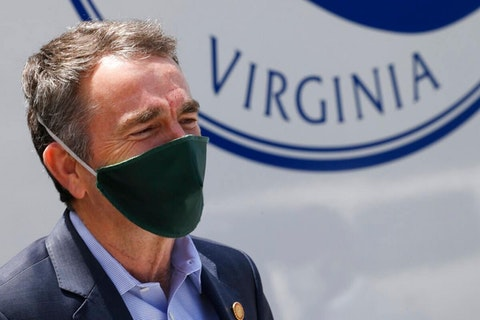 Virginia Gov. Ralph Northam listens as he prepares to speak to a group of volunteers to distribute supplies at health equity community event Tuesday May 12, 2020, in Richmond, Va. (AP Photo/Steve Helber)