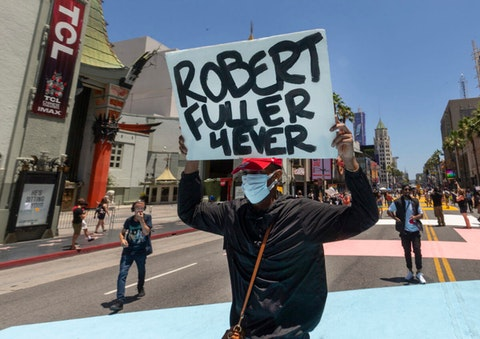 """A demonstrator carries a sign reading: """"Robert Fuller 4Ever"""" during an All Black Lives Matter march organized by black members of the LGBTQ community, in the Hollywood section of Los Angeles on Sunday, June 14, 2020. (AP Photo/Damian Dovarganes)"""