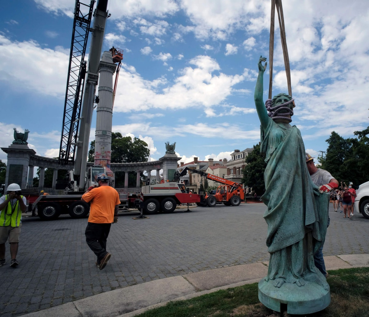 "The statue from the Jefferson Davis monument, background, stands on the median after it was removed from its pedestal on Monument Ave. in Richmond, Va., Wednesday, July 8, 2020. The figure was atop a 65 foot tall Doric column topped by a bronze figure called ""Vindicatrix,"" also known as ""Miss Confederacy,"" is the work of Edward Virginius Valentine. (Bob Brown/Richmond Times-Dispatch via AP)"