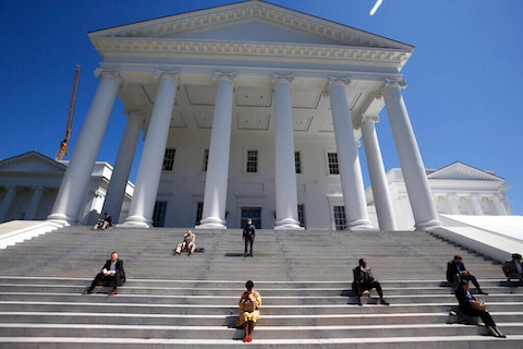House of Delegates members eat boxed lunches on the steps of the Virginia State Capitol in Richmond, Va., before the veto session began Wednesday, April 22, 2020. (Bob Brown/Richmond Times-Dispatch via AP, Pool)
