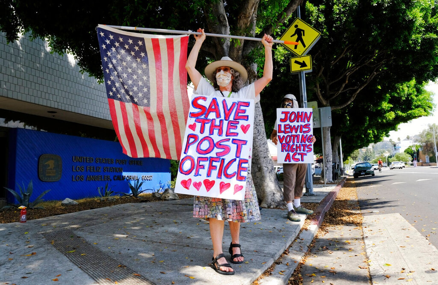 Erica Koesler, left, and David Haerle, both of Los Angeles, demonstrate outside a USPS post office, Saturday, Aug. 15, 2020, in the Los Feliz section of Los Angeles. The USPS has warned states coast to coast that it cannot guarantee all ballots cast by mail for the November election will arrive in time to be counted, even if mailed by state deadlines, raising the possibility that millions of voters could be disenfranchised.(AP Photo/Chris Pizzello)