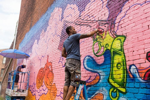 "Hamilton Glass and Matt Lively paint, ""In Conversation,"" a Richmond mural with the Mending Walls project. Photo courtesy of Katrina Boone."