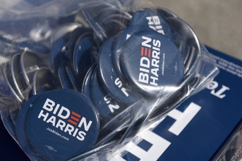 Biden/Harris pins are displayed by the Joe Biden campaign are seen on a table at an early voting satellite location at the Anne B. Day elementary school, Thursday, Oct. 15, 2020, in Philadelphia. (AP Photo/Michael Perez)