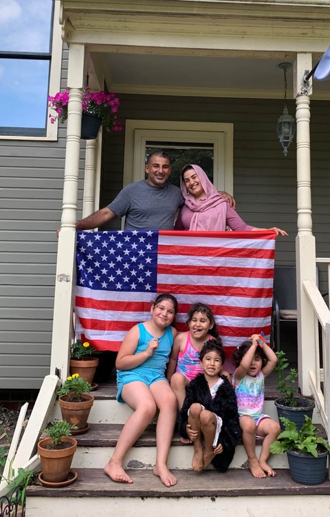 A.J. Mikhlif (top left) stands with his family on the porch stairs of their new home. Contributed photo.