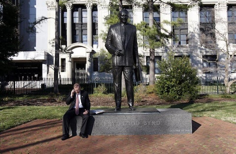 House Majority Leader H. Morgan Griffith, R-Salem, talks on a phone as he sits at the feet of the statue of former Gov. and U.S. Sen. Harry F. Byrd at Capitol Square in Richmond, Va. Saturday, March 13, 2010. A panel of Virginia legislators will discuss the removal of a statue of former governor and U.S. Sen. Harry F. Byrd Sr., from the state Capitol grounds. Byrd was a staunch segregationist and the architect of massive resistance against integrating schools. (Bob Brown/Richmond Times-Dispatch via AP)