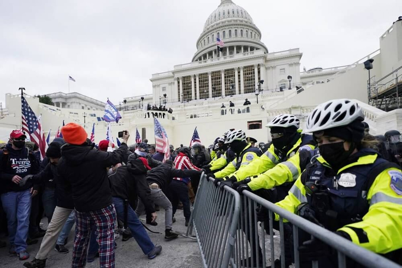 rump supporters try to break through a police barrier, Wednesday, Jan. 6, 2021, at the Capitol in Washington. As Congress prepares to affirm President-elect Joe Biden's victory, thousands of people have gathered to show their support for President Donald Trump and his claims of election fraud. (AP Photo/Julio Cortez)