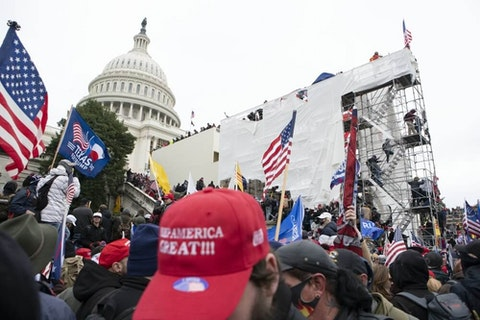 Supporters of President Donald Trump climb on an inauguration platform on the West Front of the U.S. Capitol on Wednesday, Jan. 6, 2021, in Washington. (AP Photo/Jose Luis Magana)