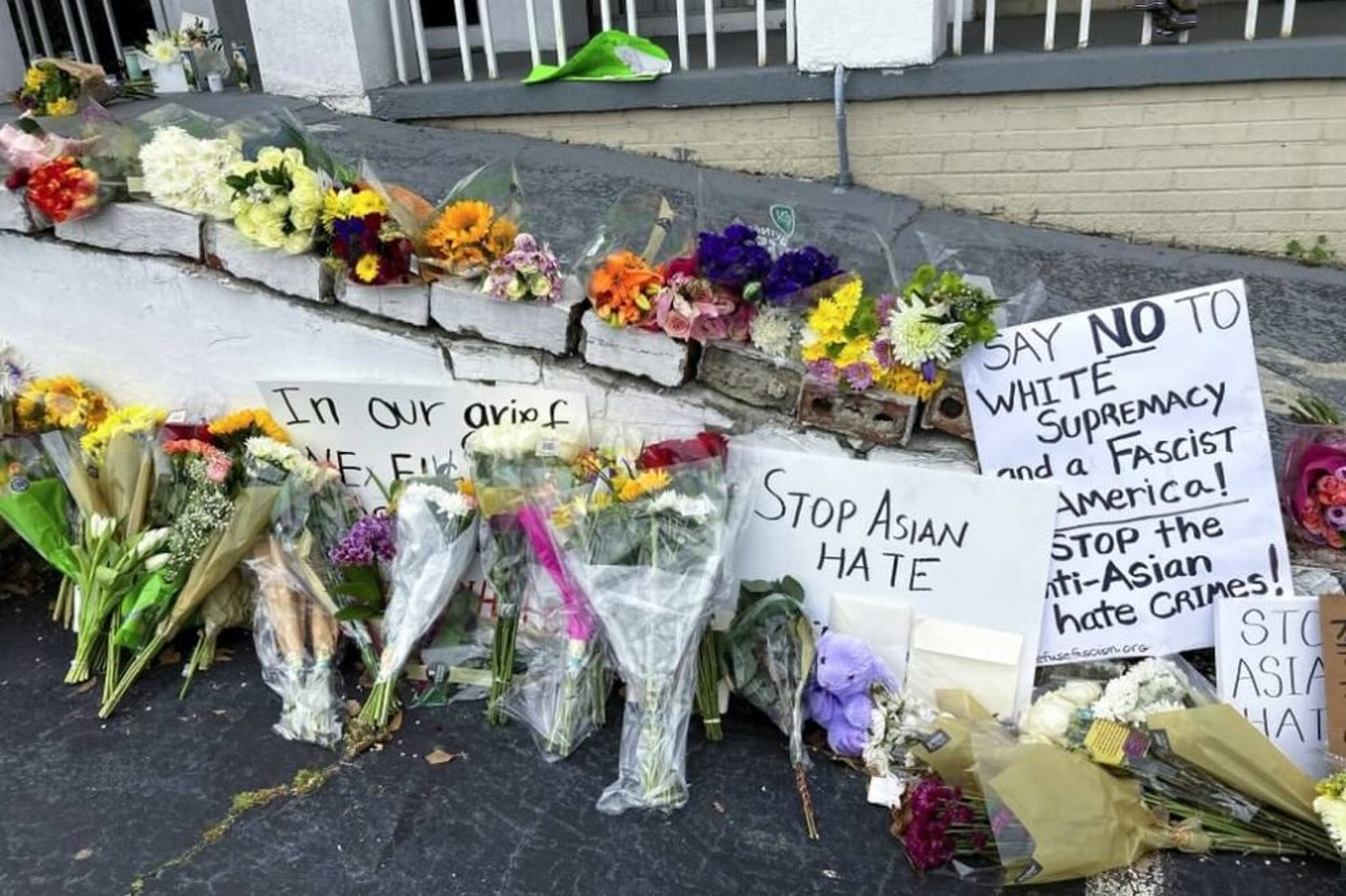 FILE - In this March 19, 2021, file photo, flowers, candles and signs are displayed at a makeshift memorial in Atlanta. A deadly rampage at three Georgia massage businesses, where the employees were mostly of Asian descent, has prompted Asian American women to openly share stories of being sexually harassed or demeaned based on their race. (AP Photo/Candice Choi, File)