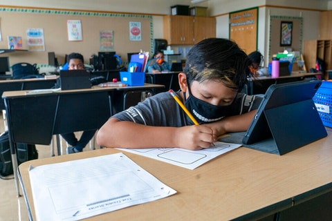 Student wearing a mask at his desk.