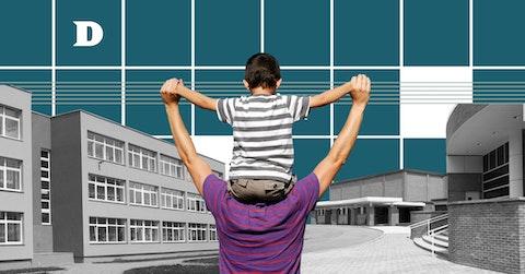 Son on father's shoulders walking towards school building.