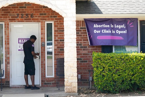 A security guard opens the door to the Whole Women's Health Clinic in Fort Worth, Texas, Wednesday, Sept. 1, 2021. A Texas law banning most abortions in the state took effect at midnight, but the Supreme Court has yet to act on an emergency appeal to put the law on hold. If allowed to remain in force, the law would be the most dramatic restriction on abortion rights in the United States since the high court's landmark Roe v. Wade decision legalized abortion across the country in 1973. (AP Photo/LM Otero)