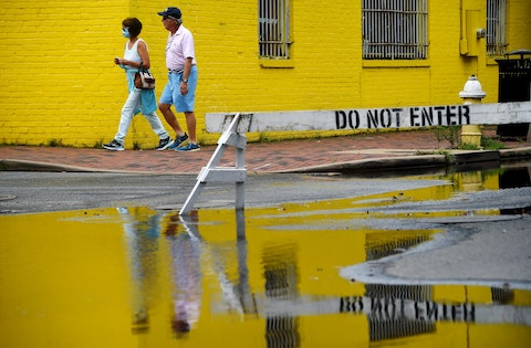 People walk past a flooded street in old town Alexandria, Virginia. (Photo by OLIVIER DOULIERY/AFP via Getty Images)