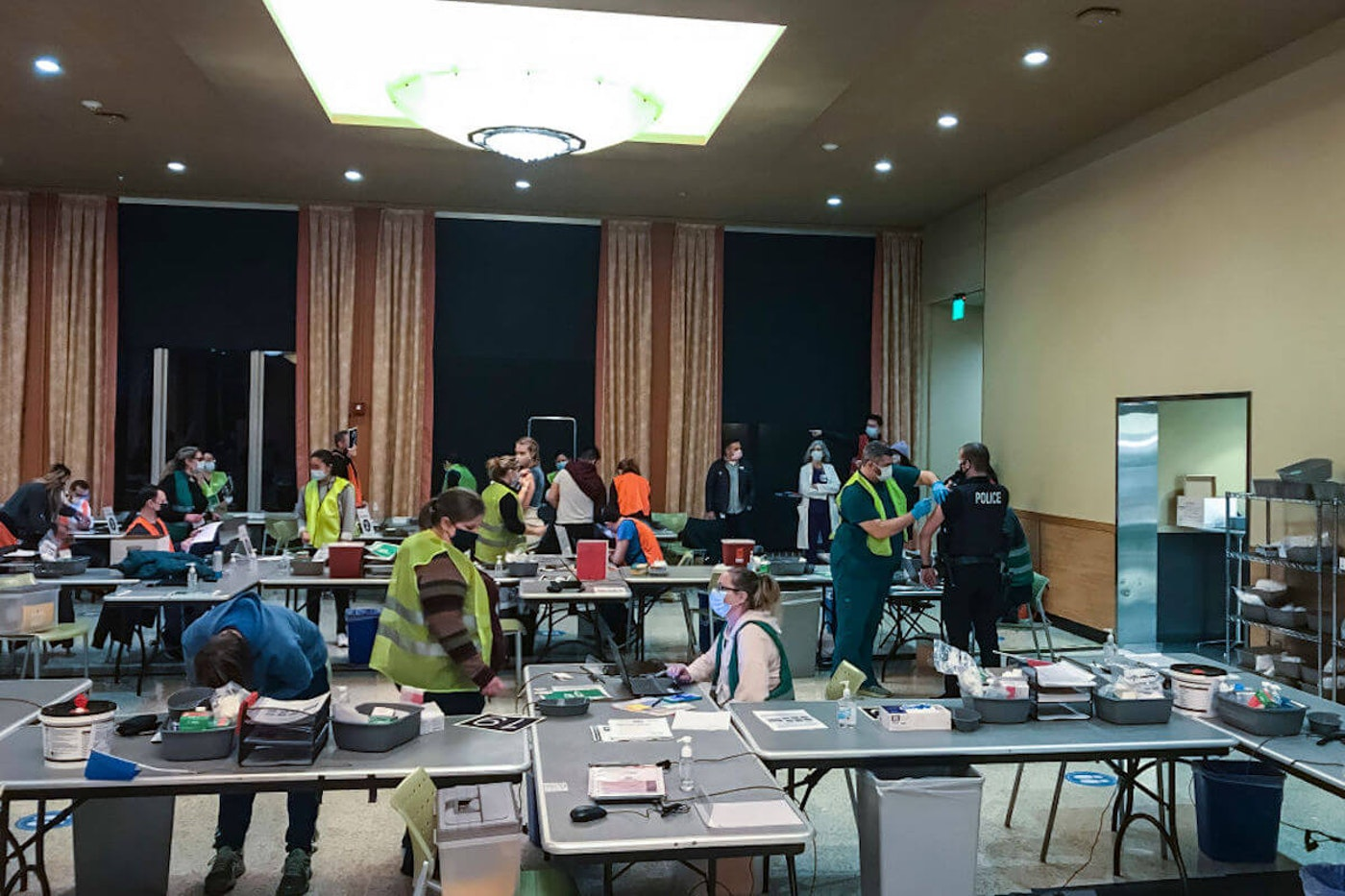 Healthcare workers in protective equipment administer vaccines to patients in a conference room with folding tables. It is after sunset.