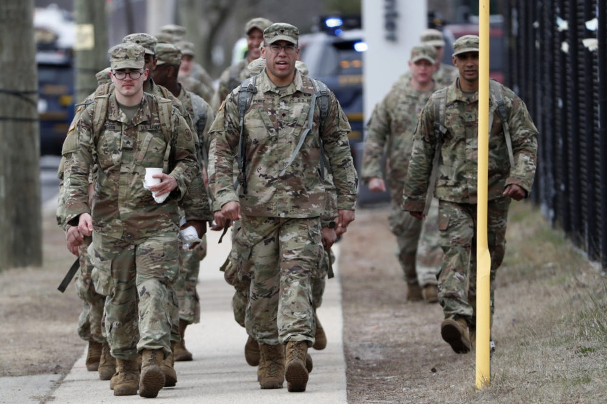 National Guard personnel march in formation as they leave duty after working Thursday, March 19, 2020, at a state-managed coronavirus drive-through testing site that just opened on Staten Island in New York. (AP Photo/Kathy Willens)