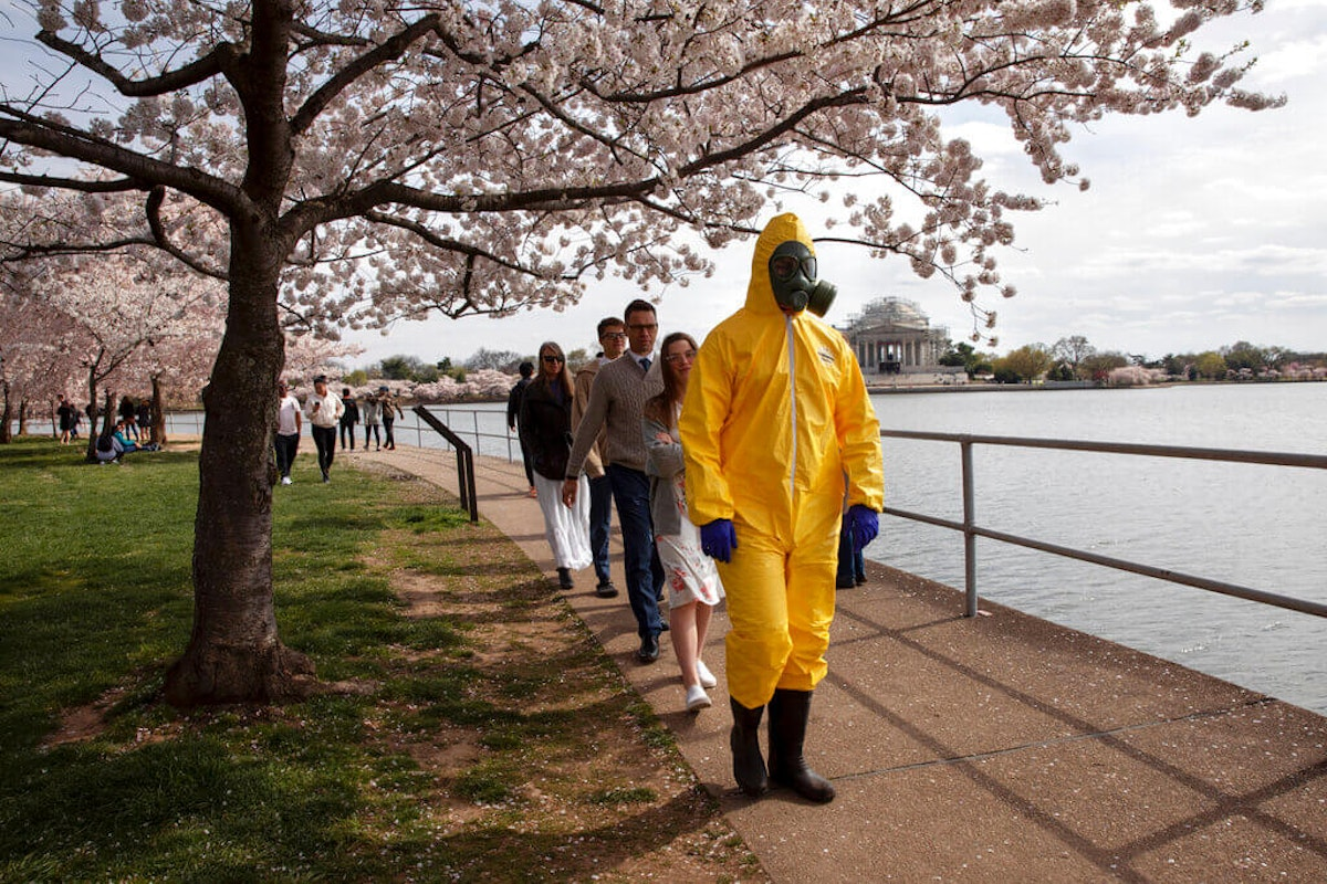 """A 17-year-old who asked not to be named wears a yellow hazmat suit, gas mask, boots, and gloves as he walks with his family, from Gaithersburg, Md., under cherry blossom trees in full bloom along the tidal basin, Sunday, March 22, 2020, in Washington. """"I'm not worried for me since I'm young,"""" says the 17-year-old, """"I'm wearing this in case I come into contact with anyone who is older so that I won't be a threat to them."""" He plans to wear his protective outfit for coronavirus each time he leaves the house. (AP Photo/Jacquelyn Martin)"""