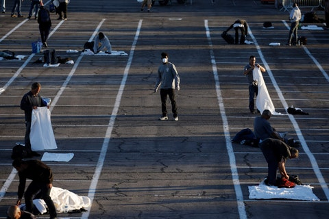 People prepare to sleep in areas marked by painted boxes on the ground of a parking lot at a makeshift camp for the homeless in Las Vegas. (AP Photo/John Locher)