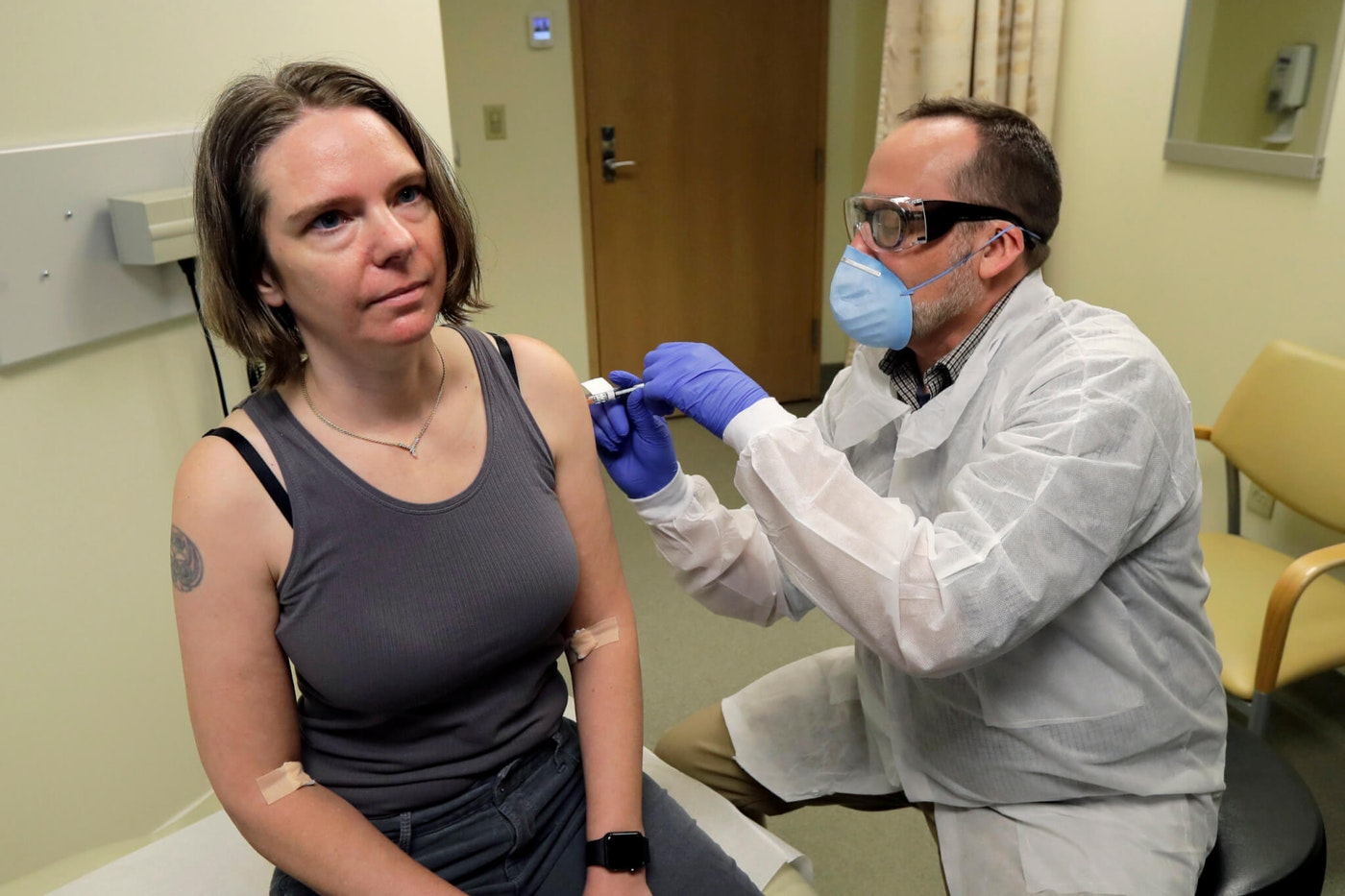 A pharmacist gives Jennifer Haller, left, the first shot in the first-stage safety study clinical trial of a potential vaccine for COVID-19. (AP Photo/Ted S. Warren)