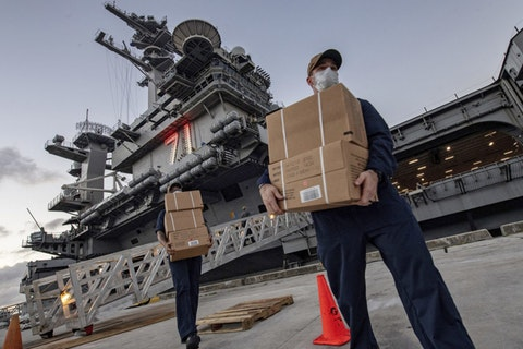 In this April 7, 2020, photo released by the U.S. Navy, sailors assigned to the aircraft carrier USS Theodore Roosevelt move ready to eat meals for sailors who have tested negative for COVID-19 and are being taken to local hotels in an effort to implement social distancing at Naval Base Guam.  (Mass Communication Specialist Julio Rivera/U.S. Navy via AP)