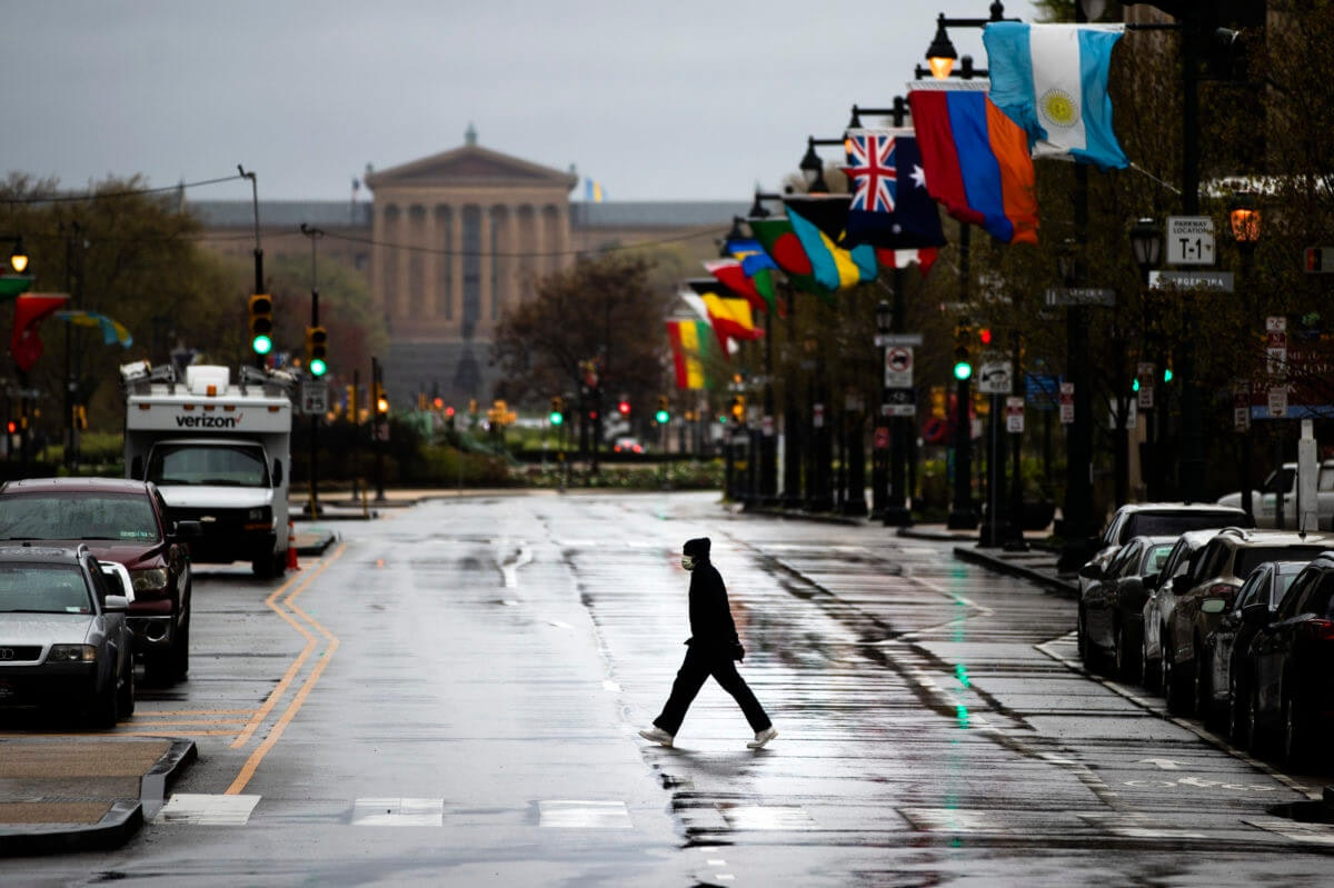 A person wearing a protective face mask crosses Benjamin Franklin Parkway in view of the Philadelphia Museum of Art in Philadelphia, Monday, April 13, 2020. (AP Photo/Matt Rourke)
