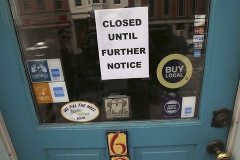 A closed sign hangs in the window of a shop in Portsmouth, N.H., due to coronavirus concerns.  (AP Photo/Charles Krupa, File)