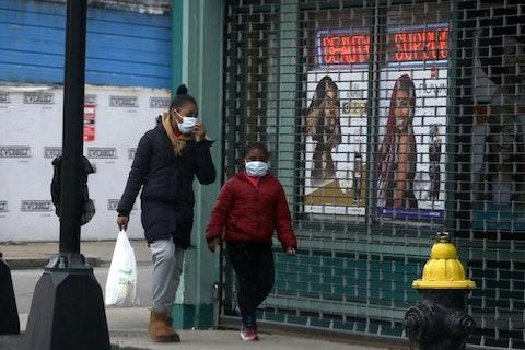 Passers-by walk past a closed shop, in Boston. (AP Photo/Steven Senne)