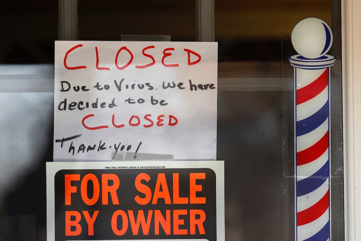 A For Sale By Owner and closed due virus sign are shown at Images On Mack in Grosse Pointe Woods, Michigan. (AP Photo/Paul Sancya)