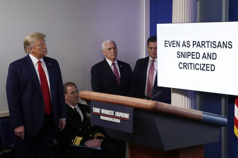 President Donald Trump watches as a White House produced video plays during a briefing about the coronavirus in the James Brady Press Briefing Room at the White House, Monday, April 13, 2020, in Washington. (AP Photo/Alex Brandon)