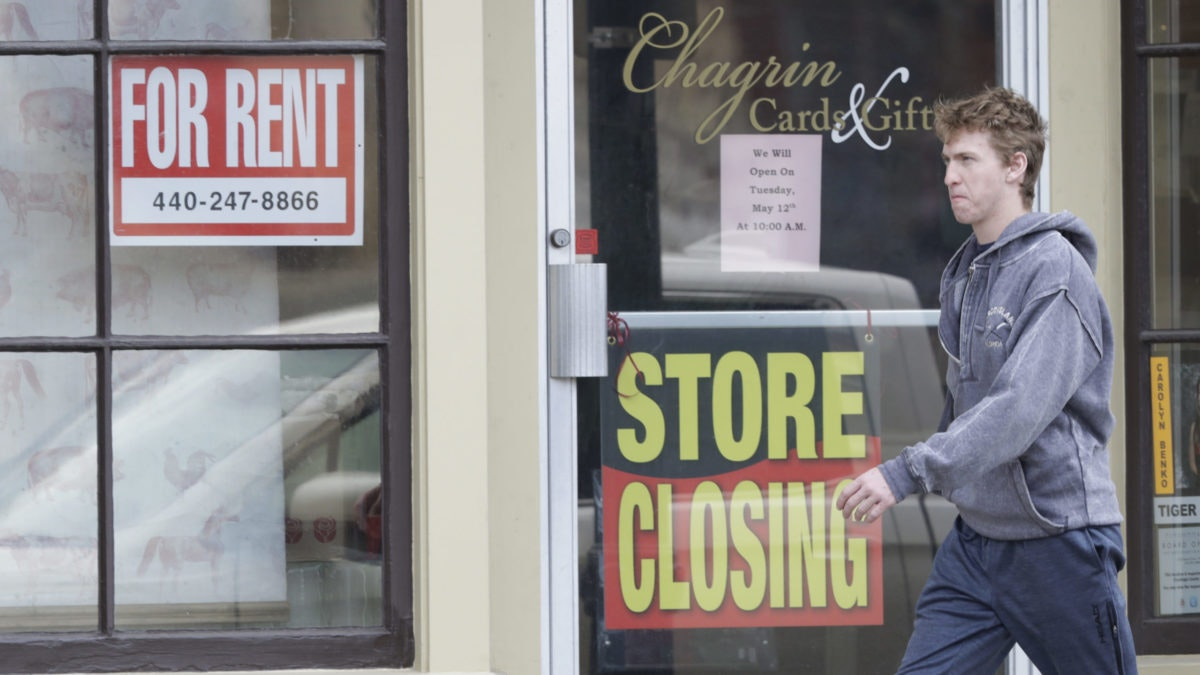 A man walks past a closed business, Wednesday, April 29, 2020, in Chagrin Falls, Ohio. (AP Photo/Tony Dejak)