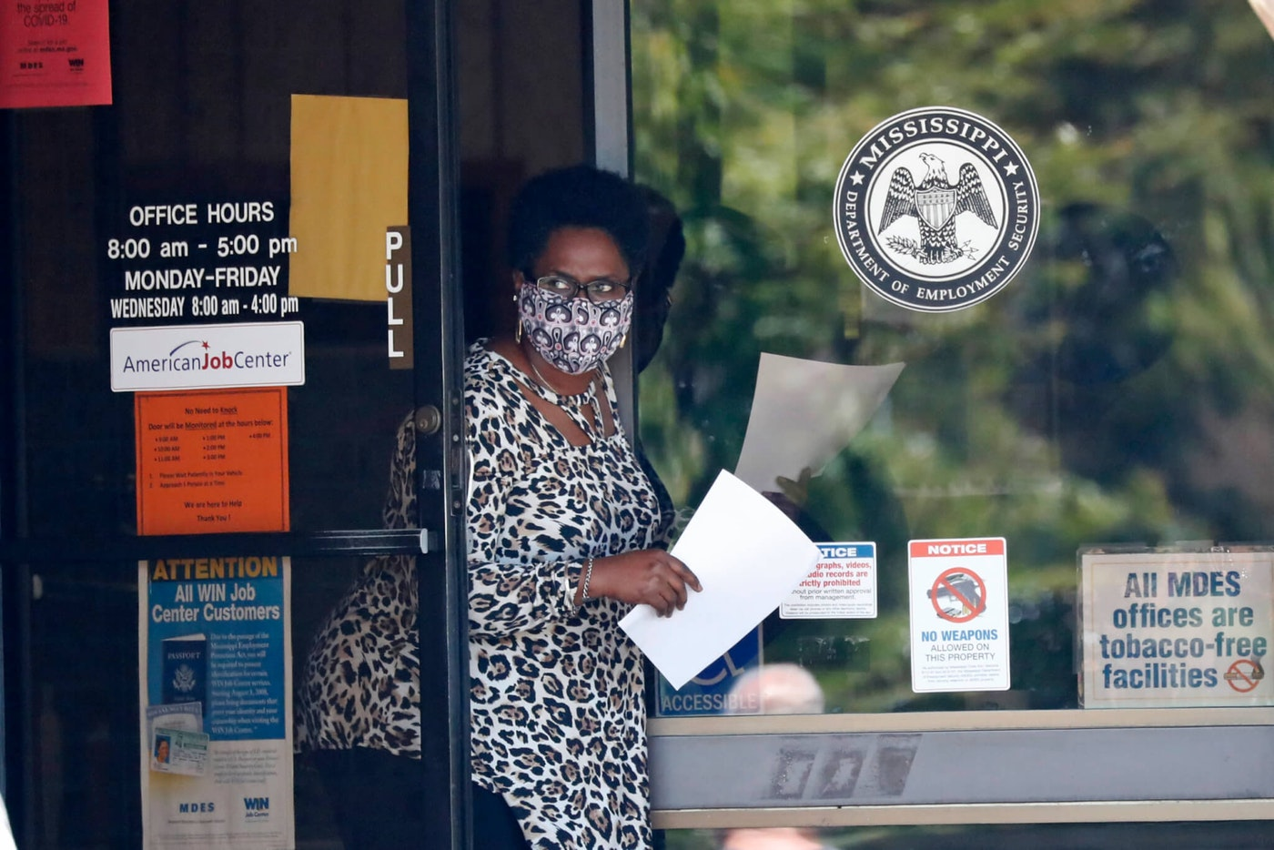 A masked worker at this state WIN job center in Pearl, Miss., holds an unemployment benefit application form as she waits for a client, Tuesday, April 21, 2020.  (AP Photo/Rogelio V. Solis)