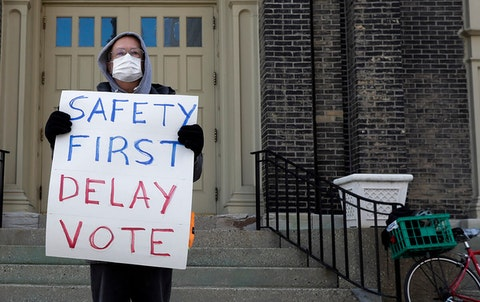 Jim Carpenter protests Tuesday's scheduled election amid the coronavirus pandemic Monday April 6, 2020, in downtown Milwaukee.  (AP Photo/Morry Gash)