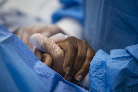 FILE - In this April 28, 2020, file photo, nurse practitioner talks to a patient and holds her hand while a doctor administers an IV at Roseland Community Hospital in Chicago. Many African Americans watching protests calling for easing restrictions meant to slow the spread of the new coronavirus see them as one more example of how their health and their rights just don't seem to matter. (Ashlee Rezin Garcia/Chicago Sun-Times via AP, File)
