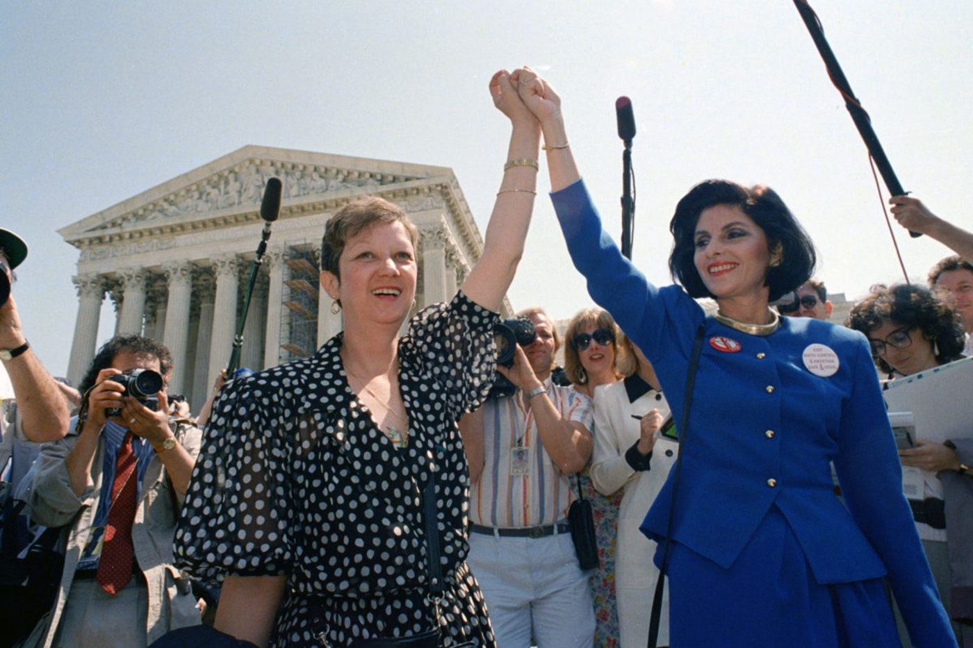 """FILE - In this April 26, 1989 file photo, Norma McCorvey, Jane Roe in the 1973 court case, left, and her attorney Gloria Allred hold hands as they leave the Supreme Court building in Washington after sitting in while the court listened to arguments in a Missouri abortion case. Three years after her death of heart failure at age 69, the woman better known as """"Jane Roe"""" is making headlines again. In a documentary being released Friday, Norma McCorvey tells the audience that her support for the anti-abortion cause was an act all along. The documentary """"AKA Jane Roe"""" premieres Friday on FX.  (AP Photo/J. Scott Applewhite, File)"""