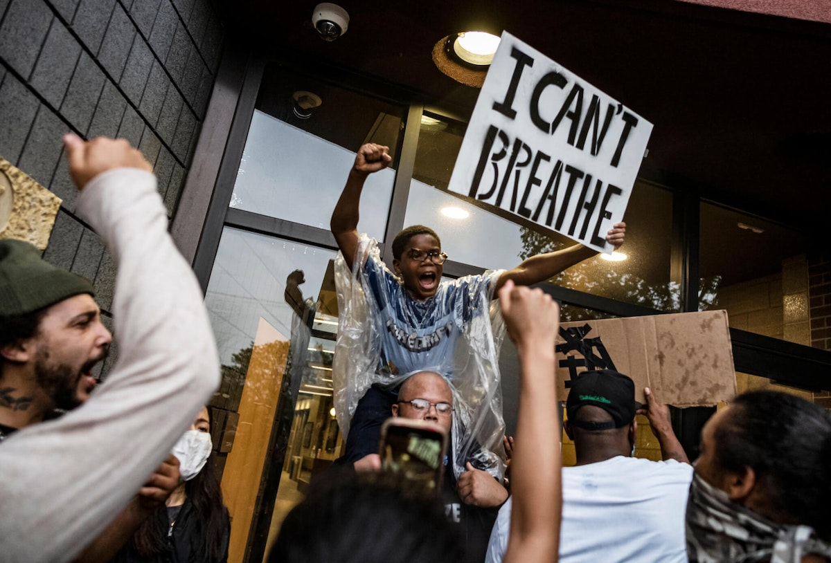 People gather at a police precinct during a protest for George Floyd in Minneapolis on Tuesday, May 26, 2020. (Richard Tsong-Taatarii/Star Tribune via AP)