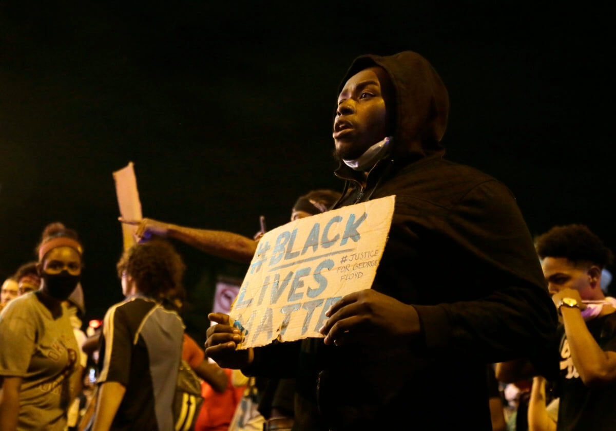 A protester holds a sign in downtown Columbus, Ohio, Thursday, May 28, 2020, during a demonstration over the death of George Floyd in police custody Monday in Minneapolis. (Barbara J. Perenic/The Columbus Dispatch via AP)