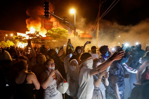 Protestors demonstrate outside of a burning liquor store near the Minneapolis 3rd Police Precinct, Thursday, May 28, 2020, in Minneapolis. (AP Photo/John Minchillo)