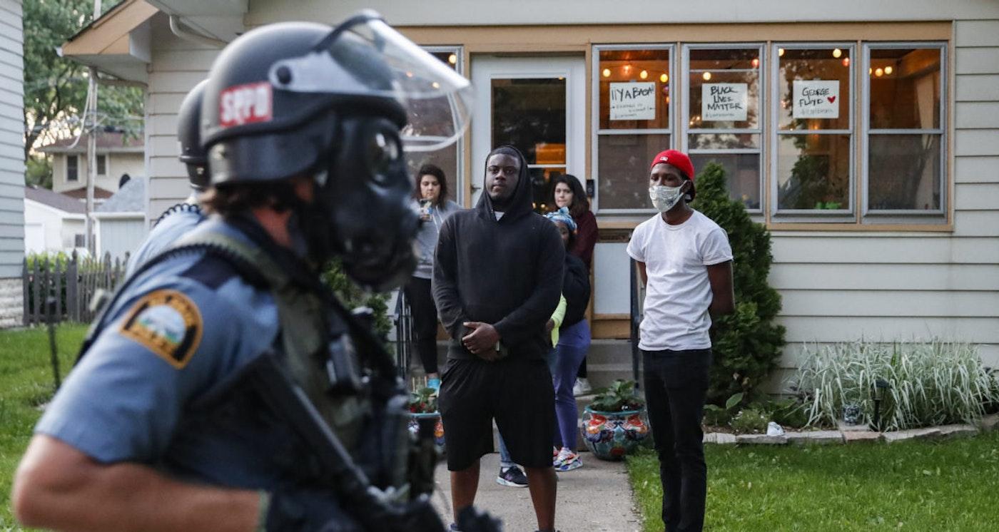 Protestors watch as police in riot gear walk down a residential street, Thursday, May 28, 2020, in St. Paul, Minn. (AP Photo/John Minchillo)