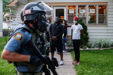 Protestors watch as police in riot gear walk down a residential street, Thursday, May 28, 2020, in St. Paul, Minn. (AP Photo/John Minchillo)