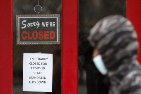 In this May 7, 2020 file photo, a pedestrian walks by The Framing Gallery, closed due to the COVID-19 pandemic, in Grosse Pointe, Mich. (AP Photo/Paul Sancya, File)